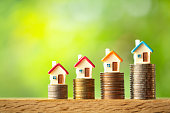 istock Four miniature house models on coin stacks on greenery blurred background 1142432526