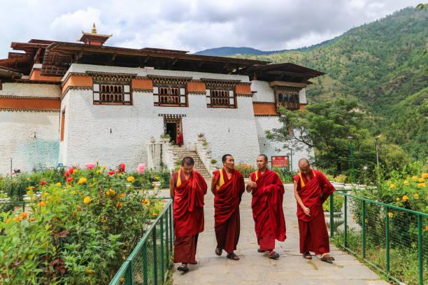 Four monks walking in the garden of Simtokha Dzong, Thimphu, Bhutan stock photo