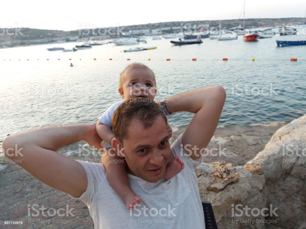 four month old baby boy sitting on daddy s neck stock photo