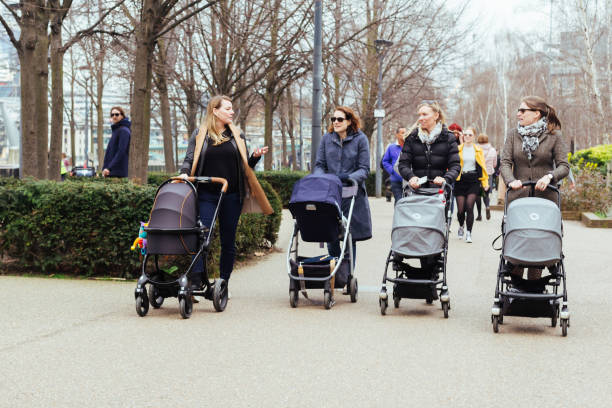 Four mothers walking with the strollers London/UK - March 25 2018: four mothers walking with the strollers along the Southbank, London baby carriage stock pictures, royalty-free photos & images