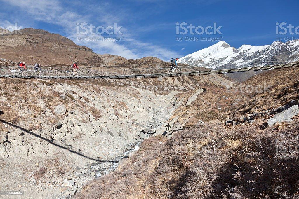 Four mountainbikers are crossing supension bridge, Nepal stock photo