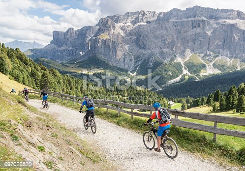 Four mountainbikers in a row are following the bike guide on a downhill in a pasture area with a huge rock face in the background in the Dolomites, Italy.  The region is popular for skiing in wintertime and hiking and mountainbiking in summertime. In August 2009, the Dolomites were declared a UNESCO World Heritage Site.