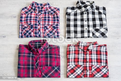 istock Four multi-colored checkered women's shirts lying neatly folded 1077660516