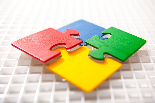 Four multicolored puzzle pieces coming together stock photo