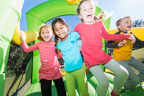 Four multi-ethnic children jumping on bouncy castle