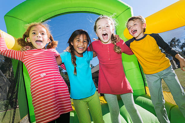 Four multi-ethnic children playing on bouncy castle stock photo