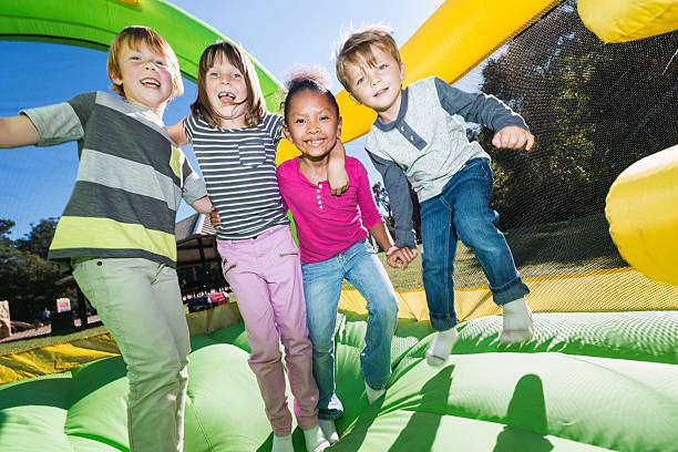 vier multi-ethnischen kinder spielen auf hüpfburg - kinderparty spiele stock-fotos und bilder