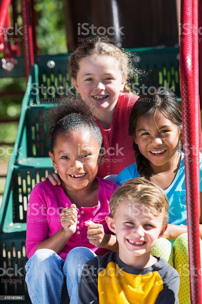 Four multi-ethnic children sitting on playground steps stock photo