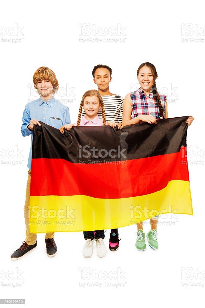 Four multiethnic teenage kids holding German flag stock photo