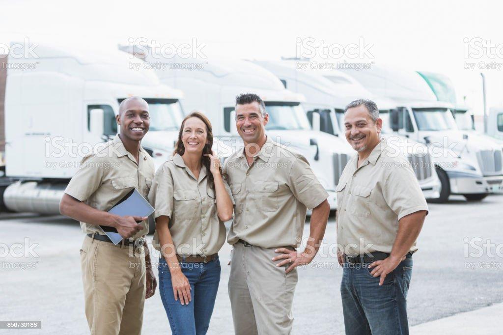 Cuatro trabajadores multiétnicos delante de semirremolques - foto de stock