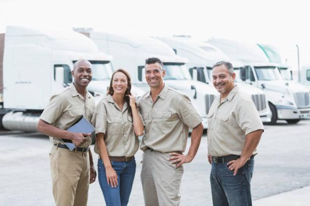 cuatro trabajadores multiétnicos delante de semirremolques - conductor de autobús fotografías e imágenes de stock