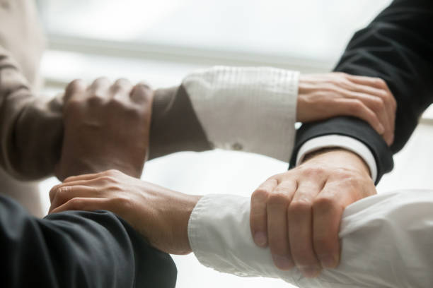four multiracial business people holding each others wrists, close up - employee engagement stock photos and pictures