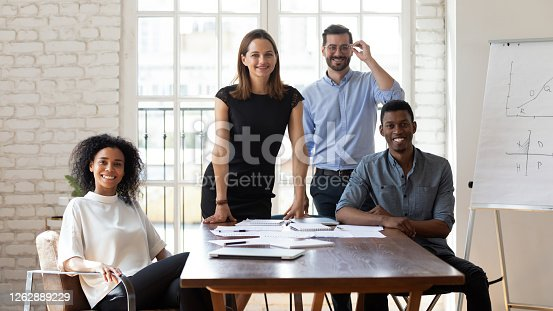 Four positive business people gather in boardroom during group meeting posing looking at camera, international company representatives portrait. Creative department workgroup, common project concept