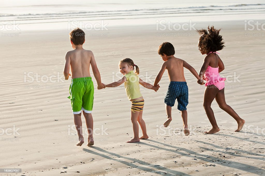 Four multiracial children holding hands and jumping at the beach stock photo