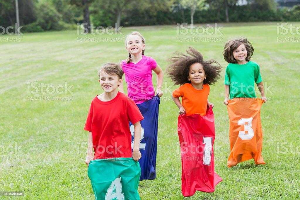 Four multiracial children in potato sack race stock photo