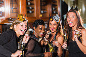 A group of four multi-ethnic women having fun at the bar of a restaurant, at a party laughing and celebrating.  They are wearing fun party hats, holding champagne flutes and blowing party horns.