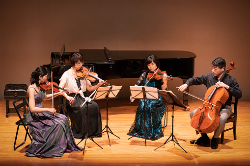 Four musicians playing violin and cello at classical music concert