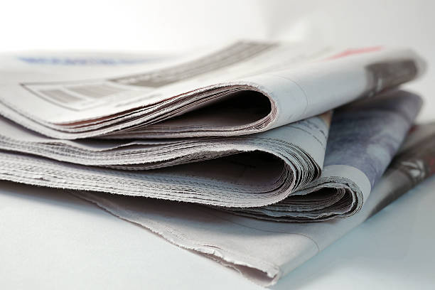 four newspapers piled up stock photo