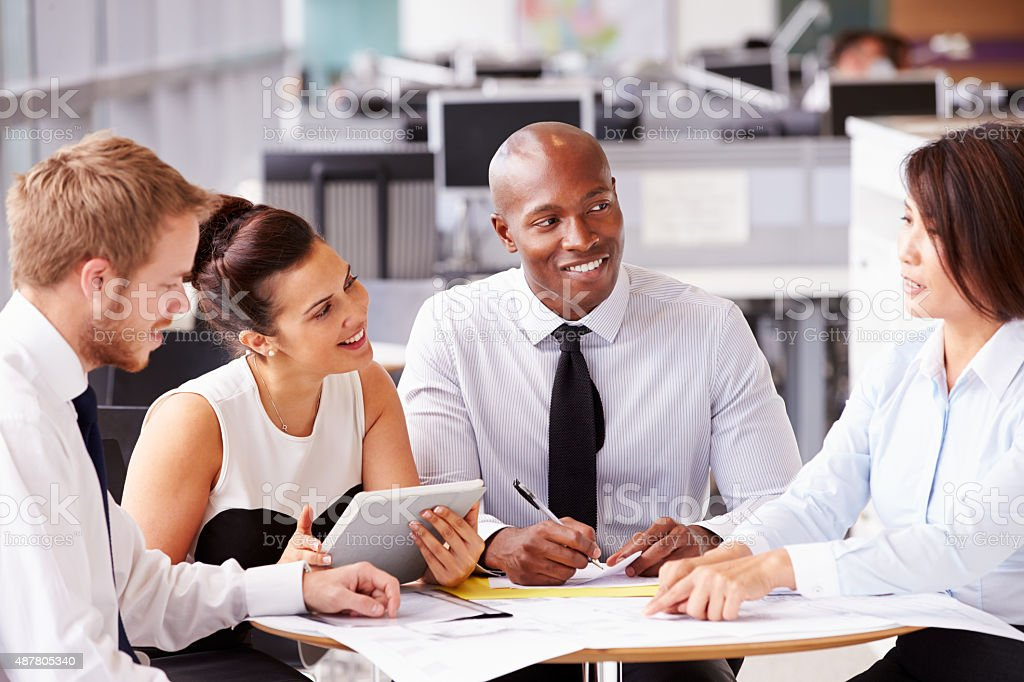 Four office colleagues in a casual team meeting stock photo