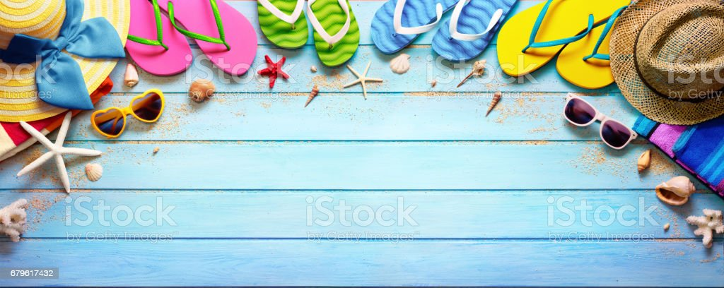 Four Pair Flip flops With Hats And Sunglasses On Wooden Plank stock photo