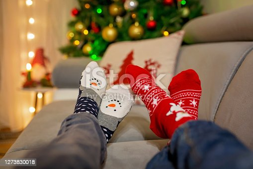 Four pair of feet in Christmas socks, mom and children lying on the couch, enjoying christmas time together