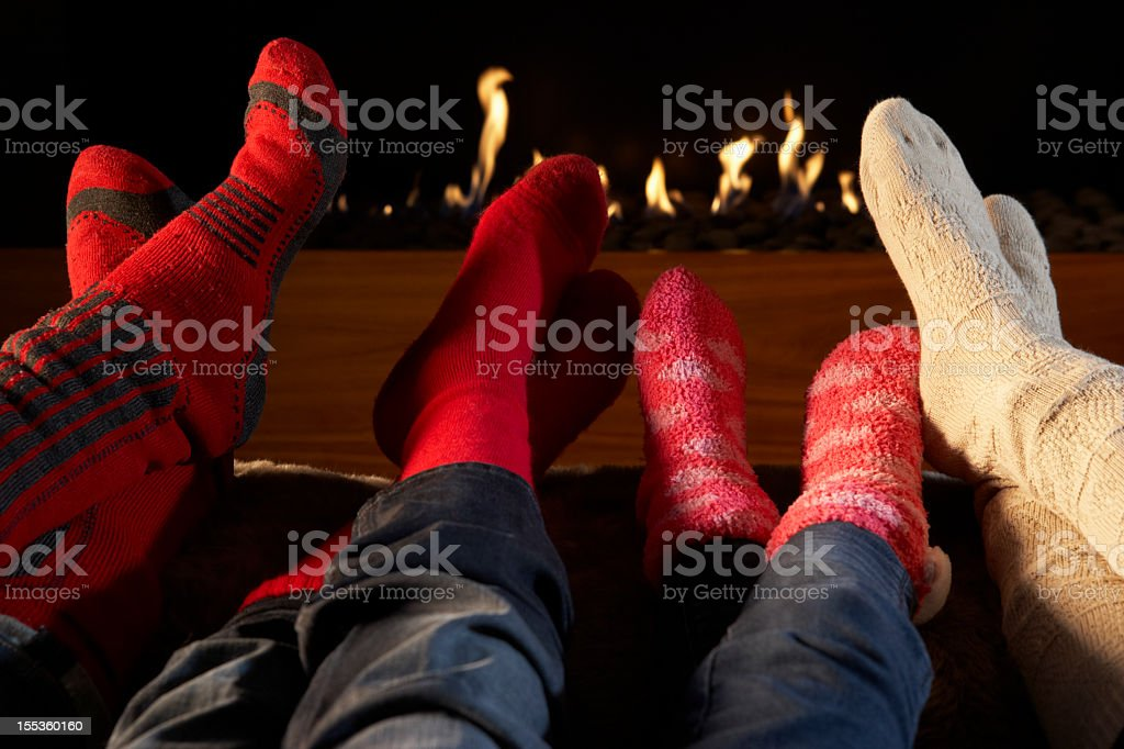 Four pairs of feet in socks warming by fire royalty-free stock photo