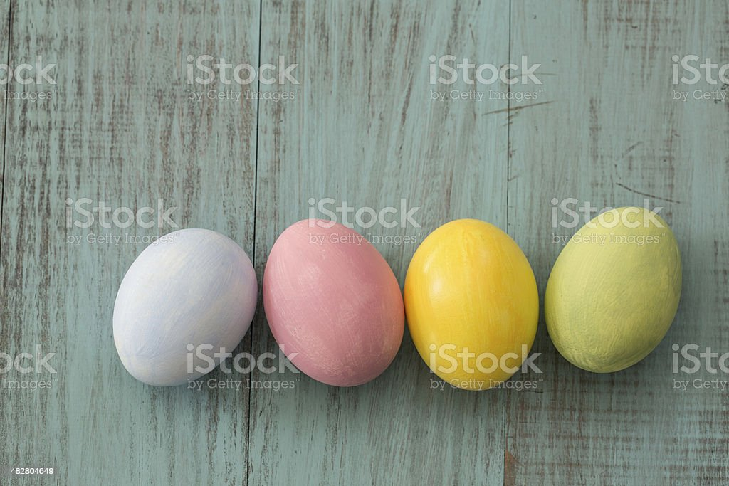 Four pastel colored Easter eggs on blue wood background stock photo
