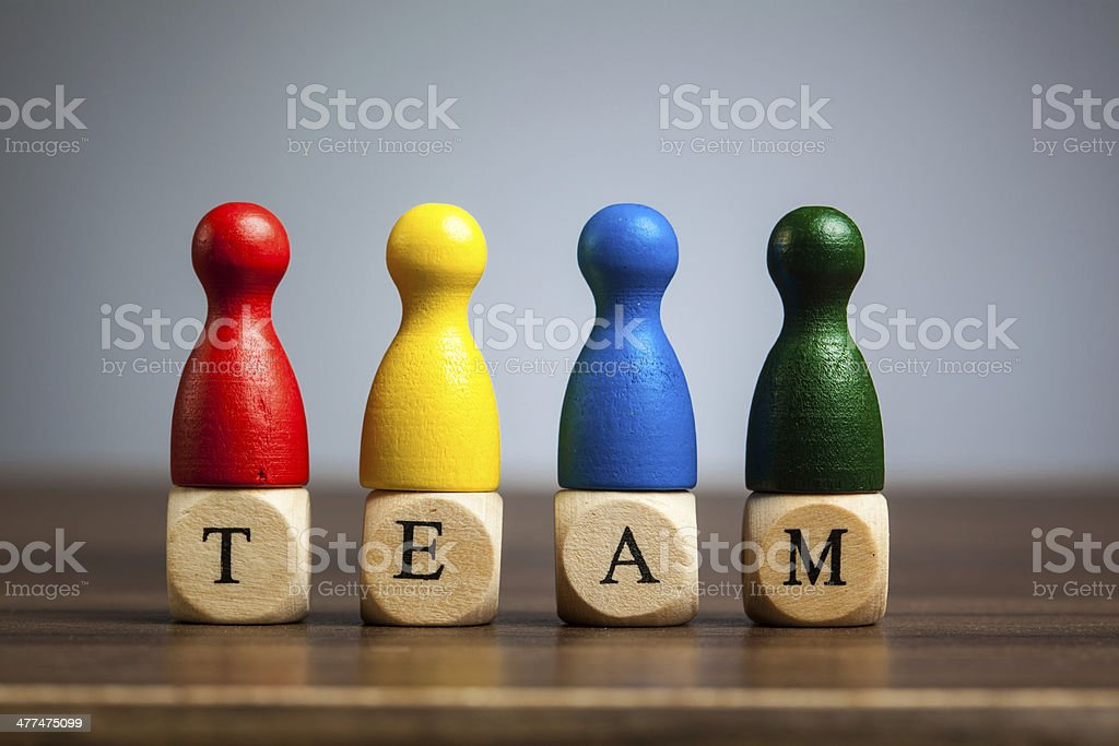 Four pawn figurines, team concept, table, grey background stock photo
