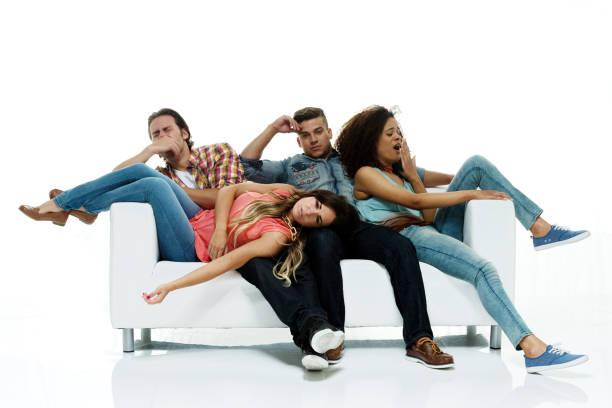 four people are tired and resting / sleeping on sofa / couch - divano procrastinazione foto e immagini stock