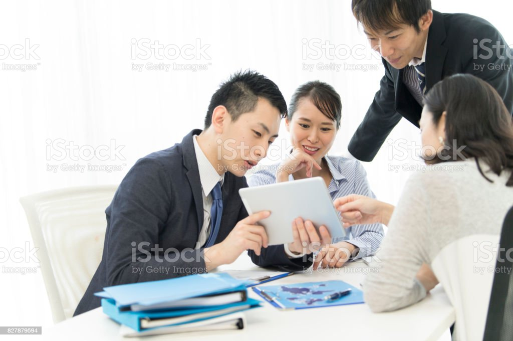 Four people are watching the tablet and talking with a smile. stock photo