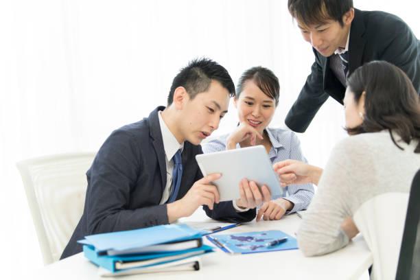4 人はタブレットを見ているし、笑顔で話しています。 - オフィスワーク ストックフォトと画像