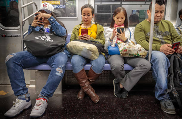 Four people checking their mobile phones in the subway stock photo