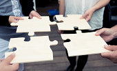 istock Four people complete a large jigsaw puzzle 175504236