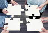 istock Four people complete a large jigsaw puzzle 480634817