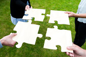 istock Four people connecting their piece of a jigsaw puzzle 187106328
