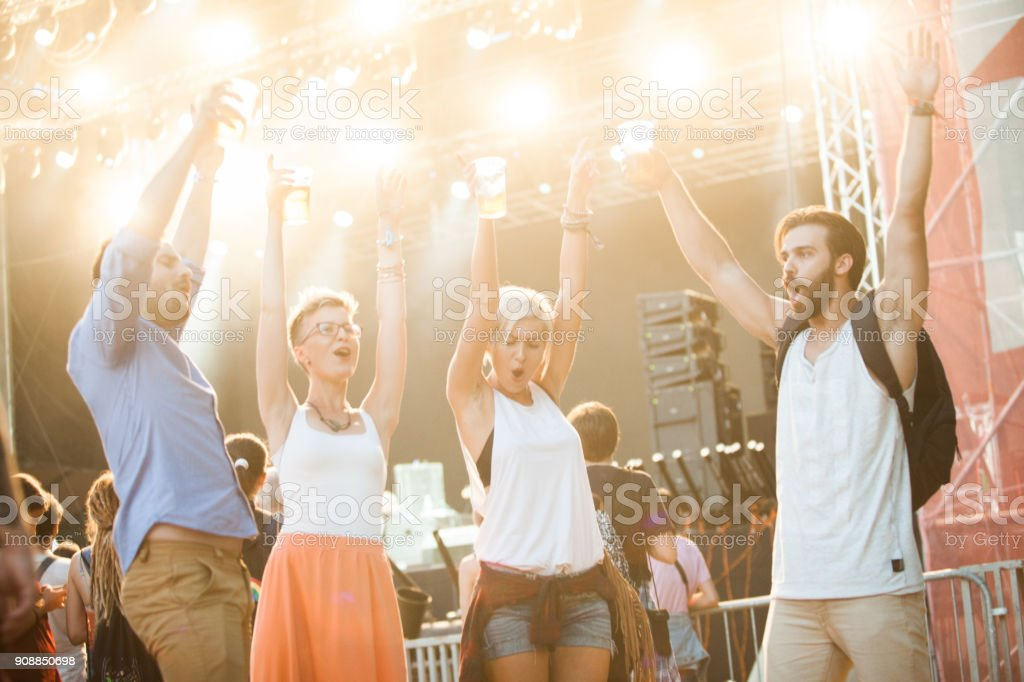 Four people dancing and drinking beer on festival stock photo