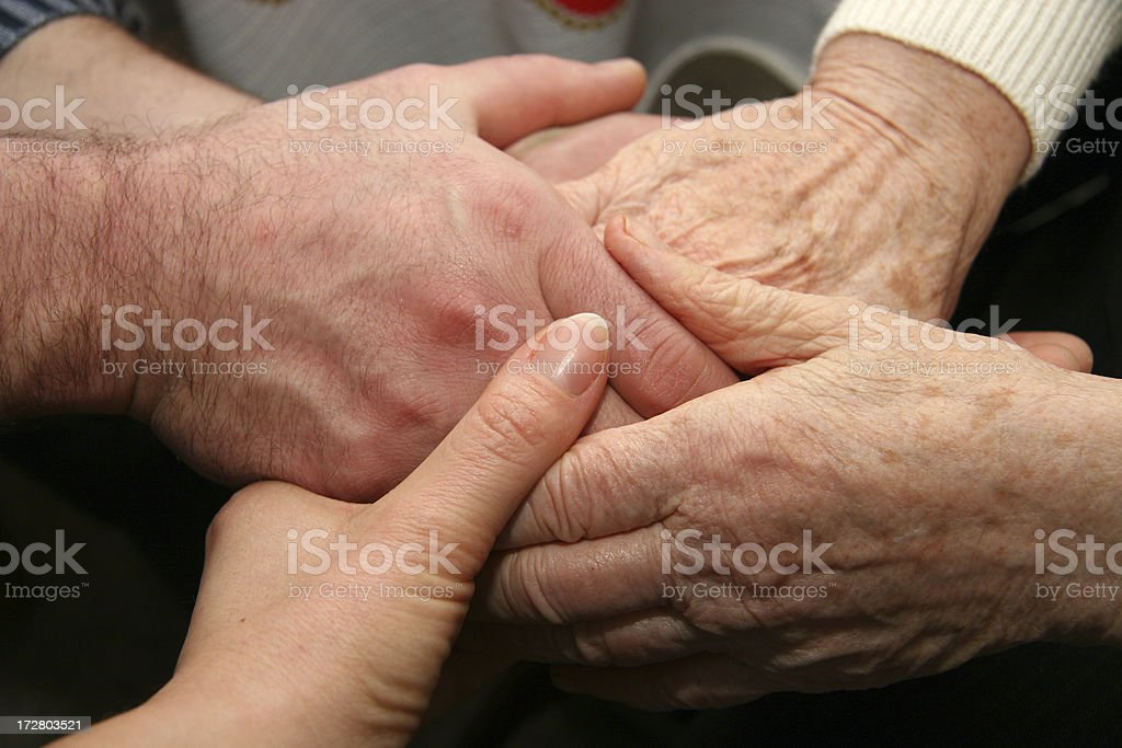 Four people holding hands together royalty-free stock photo