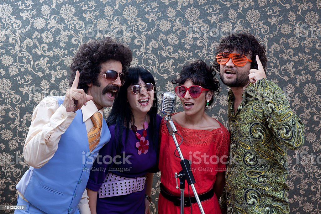 Four people in seventies style singing on old fashioned microphone royalty-free stock photo