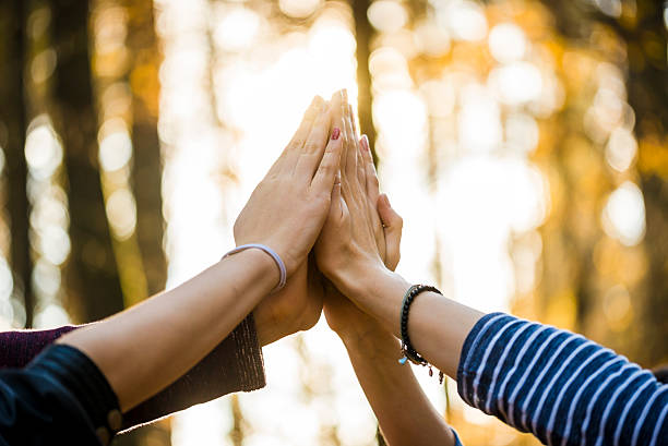 Four people joining their hands together stock photo