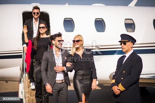 Nicely dressed celebrity people with sunglasses exiting the private jet airplane. The woman on stairs is waving to someone. Pilot in uniform is also there to escort his passengers.