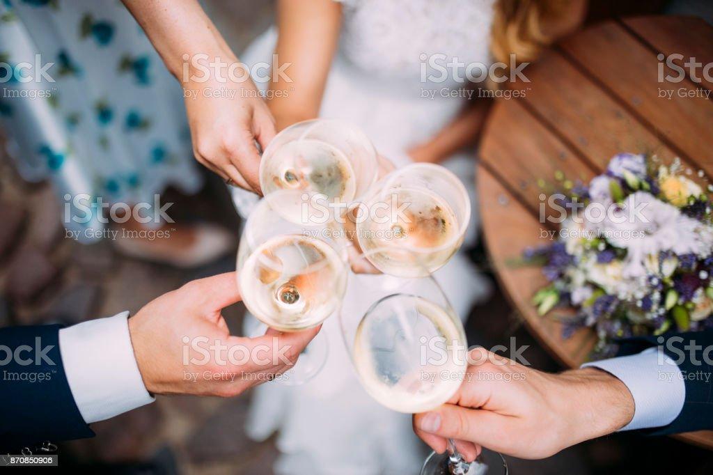 Four people make a celebratory toast on a wedding day stock photo