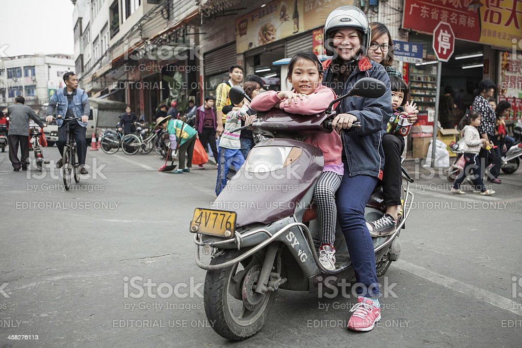 Four people on a scooter in China stock photo