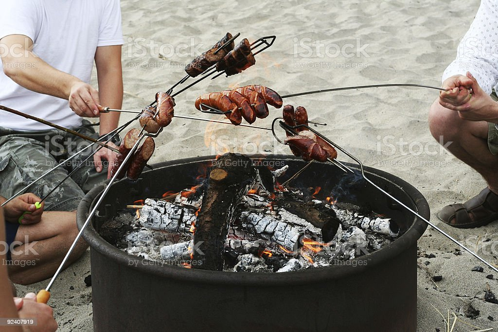 Four people sitting around a fire pit barbecuing on beach