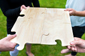 istock Four people solve a giant jigsaw puzzle 187106336