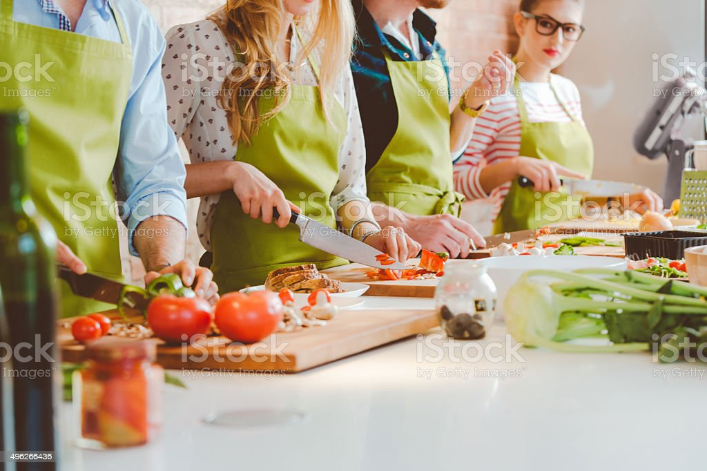 Four people taking part in cooking class stock photo