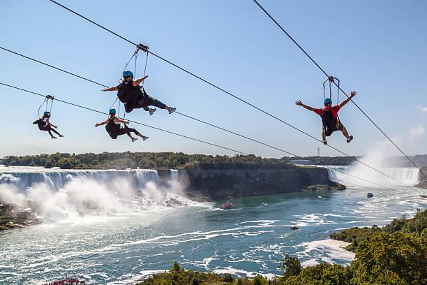 four people taking zipline ride at niagara falls, ontario, canada. - neue abenteuer stock-fotos und bilder
