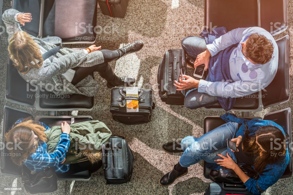 Four people waiting at an airport lobby stock photo