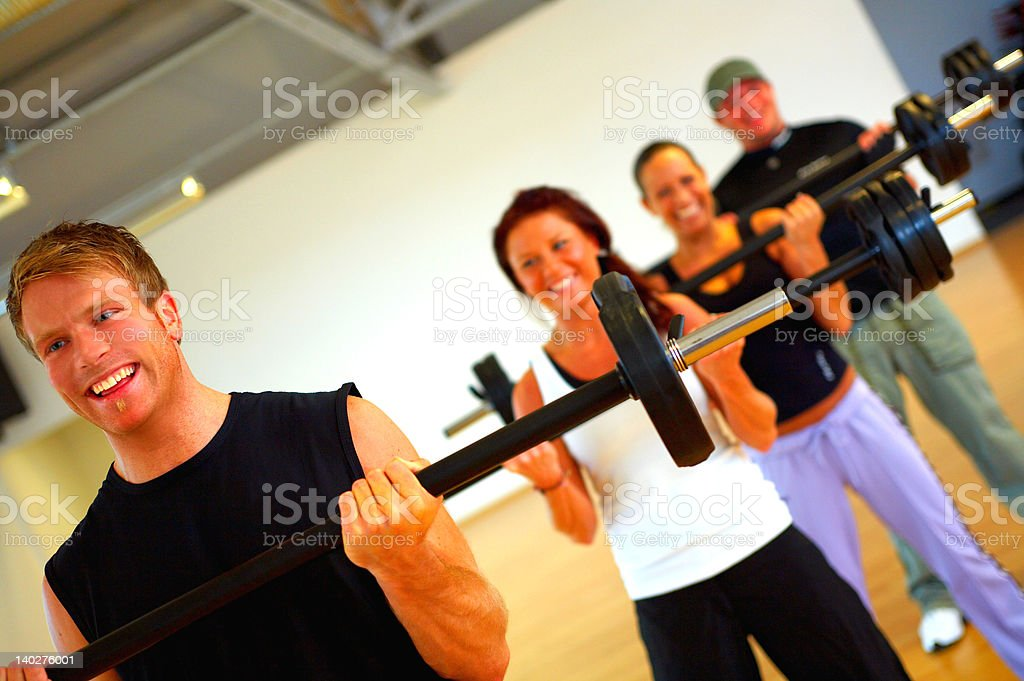 Four people weight training in a fitness center royalty-free stock photo