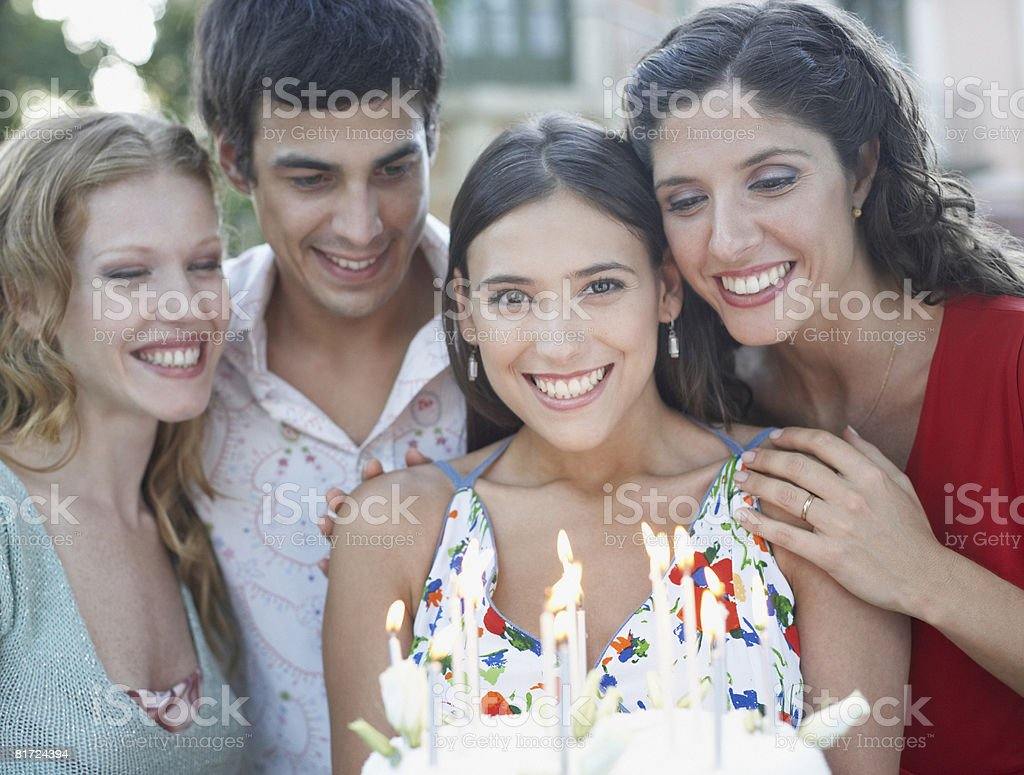 Four people with birthday cake at a party outdoors smiling royalty-free stock photo