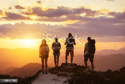 Group of four people's silhouettes stands on mountain top and looks at sunset